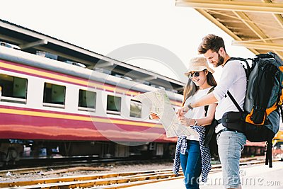 Multiethnic traveler couple using generic local map navigation together at train station platform. Asia tourism trip concept