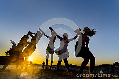 Happy young teens dancing at the beach at beautiful summer sunset