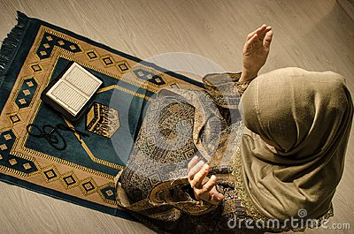 Muslim woman praying for Allah muslim god at room near window. Hands of muslim woman on the carpet praying in traditional wearing