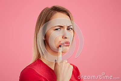 Discontent young beautiful female with unhappy look, has oral herpes, indicates at wound near lips, stands sideways against pink b