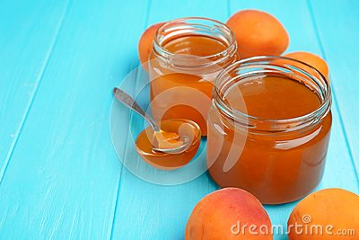Apricot jam in jars and bowl with spoon