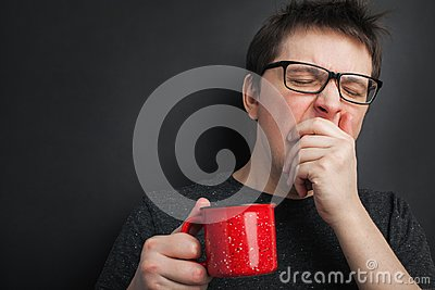 Sleepy yawning man in eyeglasses with red cup of tea or coffee has uncombed hair in underwear on black background, morning refresh