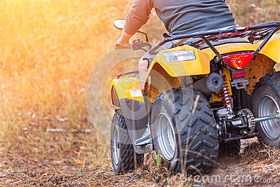 Man riding an ATV quadbike in a beautiful autumn pine forest wit