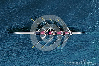 Women`s rowing team on blue water