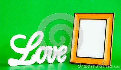 White LOVE sign and empty picture frame on green background