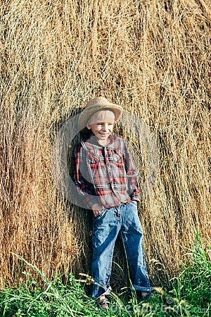 Full length portrait of boy in pose of lazy farmer, leaning hay
