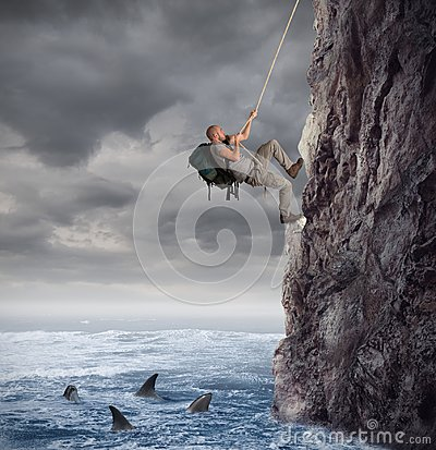 Explorer climbs a mountain with the risk to fall on the sea with sharks