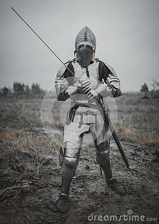 Girl in image of Jeanne d`Arc goes on meadow in armor and helmet with closed visor and sword in her hands.