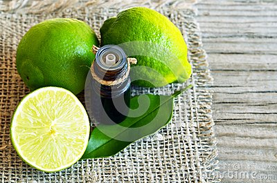 Lime essential oil in a glass bottle and fresh ripe lime fruits.Lime oil for spa,aromatherapy and bodycare.