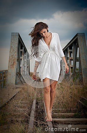 Attractive woman with short white dress and long hair standing on the rails with bridge in background. Fashion girl with sex