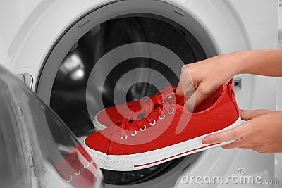 Woman putting red sneakers into washing machine