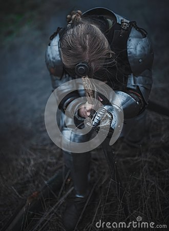 Girl in image of Jeanne d`Arc in armor and with sword in her hands kneels against background of dry grass.