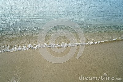 Soft pastel clean sandy beach with fresh sea water and white foamy wave line background and copyspace on Ornos shore