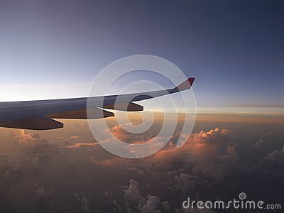Aerial view from airplane, seeing plane`s wing and pink sunset light from left side