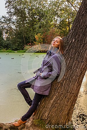 Young girl is standing near large tree, near pond in urban park in autumn evening.