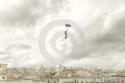 Surreal moment of a woman flying with her umbrella over the city