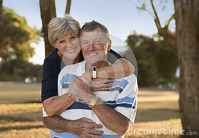 Portrait of American senior beautiful and happy mature couple around 70 years old showing love and affection smiling together in t