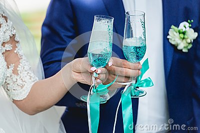 Gorgeous bride and groom toasting with champagne, wedding morning. hands holding stylish glasses of blue wine