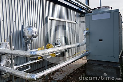 Insulated pipelines connecteed to the gray industrial cooling unit standing outdoor on the ground near to the modern fabrication b
