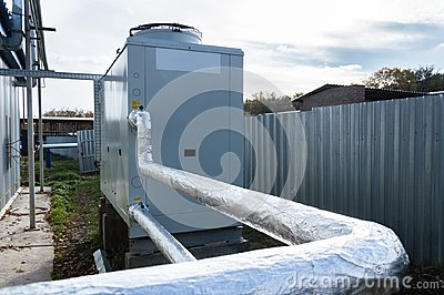 Insulated pipelines connecteed to the gray industrial chiller standing outdoor on the ground near to the modern production buildin