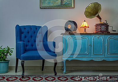 Blue armchair, vintage wooden light blue sideboard, lighted antique table lamp, old phonograph gramophone and vinyl records