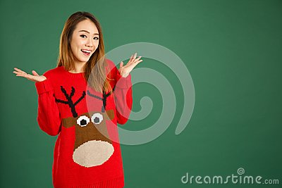 Pretty young singaporean girl wearing Christmas jumper and smiling