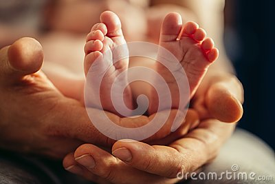 Newborn baby legs in mothers lovely hand with soft focus on babie`s foot