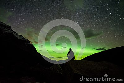 Man sitting on a rock in the mountains watching the Northern Lights