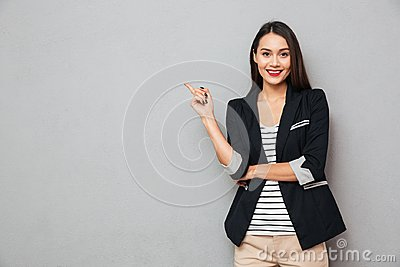Smiling asian business woman pointing up and looking at camera