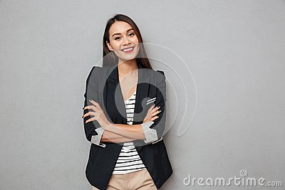 Pleased asian business woman with crossed arms looking at camera
