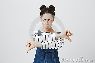 Dissatisfied angry furious girl with hairbuns in denim overalls giving two thumbs down gesture, expressing her
