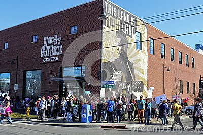People gather by mural on that says This Machine Kills Fascists at Woody Guthrie Center at Womens March in Tulsa Oklahoma USA 1-20