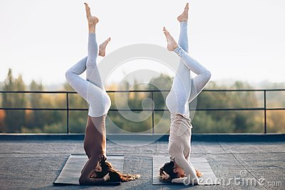 Two young women doing double yoga asana supported headstand