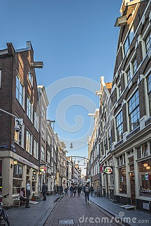 stock image of amsterdam, narrow street, in the center. all day life with the shops people with shopping bags, bicycles, outdoor shopkeepers and