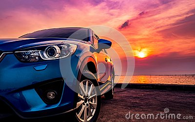 Blue compact SUV car with sport and modern design parked on concrete road by the sea at sunset. Environmentally friendly