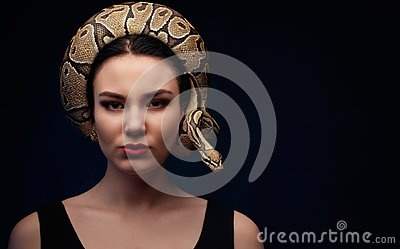Close up portrait of woman with snake around her head on dark ba