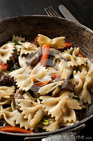 Fresh cooked pasta with mushrooms and vegetables in a pan, horiz