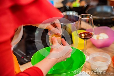 Female hands add egg in plastic bowl