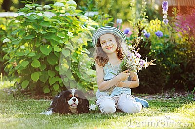 Happy child girl relaxing in summer garden with her spaniel dog, wearing gardener hat and holding bouquet of flowers.