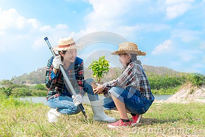 Asian Mom and child girl plant sapling tree in the nature spring for reduce global warming growth feature,