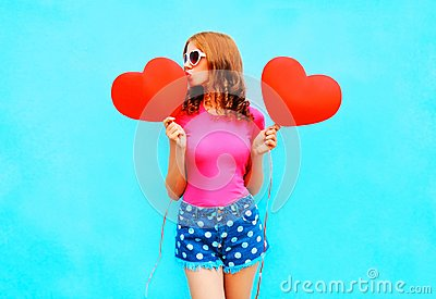 Pretty woman kisses a red balloon in the shape of heart on blue
