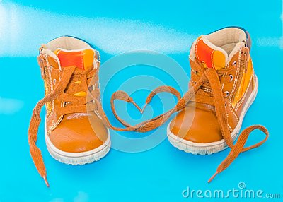 On a blue background, two children`s Shoe laces in the shape of