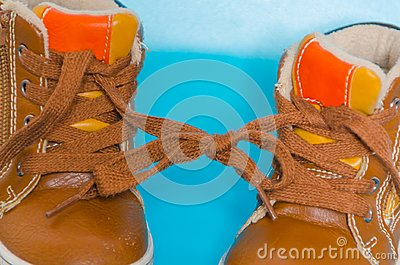 Two children`s Shoe on a blue background, tied knot