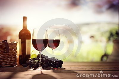 Red wine bottle and glass on table in vineyard Tuscany Italy