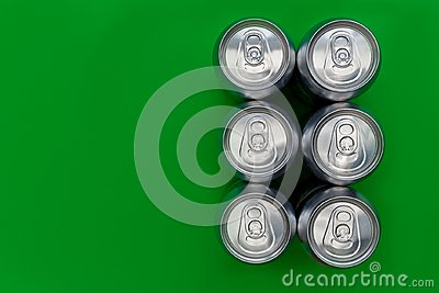 Silver metal drinks cans on green background