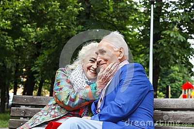Elderly family couple talking on a bench in a city park. Happy seniors dating