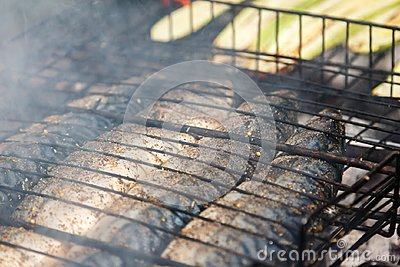 Mackerel fish roast on grill barbecue with vegetables, bonfire coals with fire,