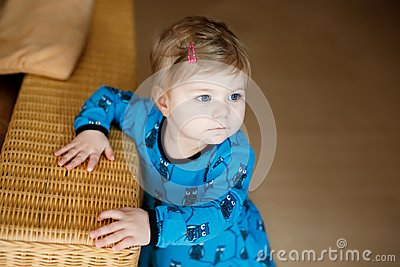 Portrait of little cute baby girl learning walking and standing. Adorable toddler girl at home