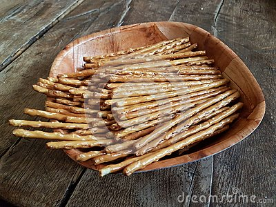Salted chopsticks on a wooden plate. Deliciuse snack for a beer on the wooden table of old style. Food of breack time.