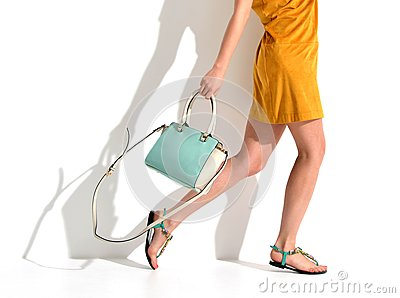 Beautiful female legs wearing summer shoes in brown yellow designers dress and blue mint woman clutch bag